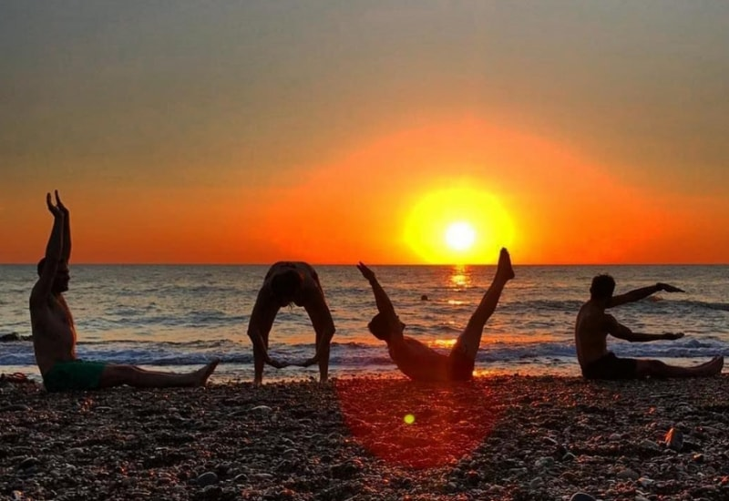 people doing yoga on greystones beach